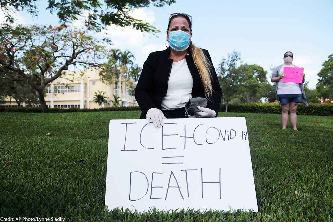A woman wears a protective face mask and gloves as she protests outside of a U.S. Immigration and Customs Enforcement field office Friday, May 29, 2020, in Plantation, Fla.